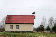 White country house trimmed with siding with windows and a red roof with a weather vane in the form of a rider on a horse in the b. Ackground of trees stock photo