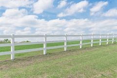 Country style wooden fence against cloud blue sky. White country style wooden fence against cloud blue sky. White fences on green grass at farm ranch land field royalty free stock photo