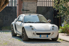 Sportcar Smart Roadster coupe outdoor in Pisa, Italy. White coupe sportcar Smart Roadster in the back yard closeup. Two-door two-seater sports car was first Stock Photography