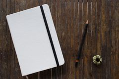 White cover notebook with black pencil on rustic wooden table flat lay photo. Stock Photo