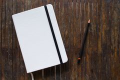 White cover notebook with black pencil on rustic wooden table flat lay photo. Closed notebook with blank cover flat lay photo. Notepad on table top view Stock Photos
