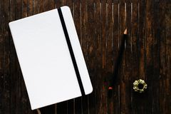 White cover sketchbook with black pencil on rustic wooden table flat lay photo. Closed notebook with blank cover flat lay photo. Notepad on table top view Stock Photos