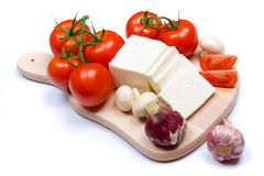 White cow cheese. White cheese slices with tomato, mushrooms and garlic isolated on white Royalty Free Stock Photography