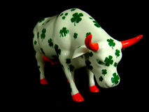 Small porcelain cow on black background Royalty Free Stock Image