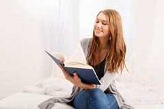 Beautiful girl, reading a book, concepts of home and comfort, place for text stock photography