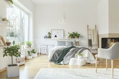 White cozy bedroom interior. Plant and white armchair in cozy bedroom interior with green and grey bedding on bed stock photos