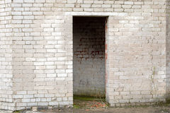 White cracked brick wall with a doorway Stock Images