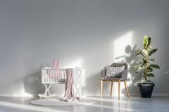 White cradle with pink blanket. And bunny pillow standing on a round rug, next to a gray armchair and ficus in basic child room interior stock photos