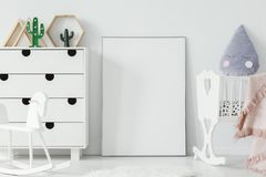 White cradle and rocking horse in bright baby`s room interior wi stock image
