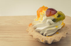 White cream cake and pieces of fruit. White cream cupcake and pieces of fruit Royalty Free Stock Image