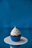 White cream chocolate cupcake with blue wrapping and on the blue background. Vertical, free space. Blurred background Stock Photo