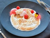 White cream desert with raspberries on black plate in restaurant. royalty free stock photo