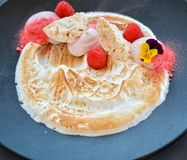White cream desert with raspberries on black plate in restaurant. royalty free stock images