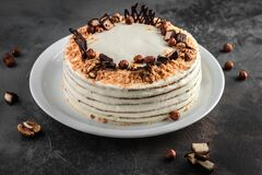Free White Cream Honey Cake With Walnuts, Hazelnuts And Sweets On Grey Cement Background, Food And Homemade Baking Concept In Rustic Stock Photos - 171716023