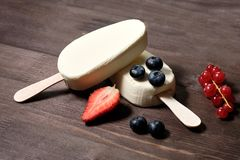 White cream ice cream on a stick with strawberries, blueberries and red currants on the dack wood background. Close up royalty free stock image