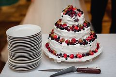 White cream wedding cake with strawberries, cherries, blueberries, black currants with three tiers. White cream wedding cake with fresh sweet strawberries Royalty Free Stock Photography