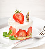 White creamy cake with strawberries on table Stock Images