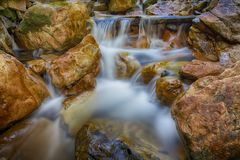 White Creamy Water and Rough Rocks. Slow exposure of a waterfall going through rocks and moss Stock Images