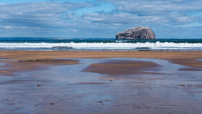 White crested waves rolling on the beach with Bass Rock in the b. Big waves crashing against a golden sandy beach with Bass Rock producly sitting in the Stock Photography