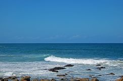 TURQUOISE SEA WITH WAVES RUSHING OVER ROCKS Royalty Free Stock Photography