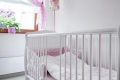 White crib in nursery room Stock Photo