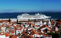 White Cruiser Boat in the Harbor of Lisbon. White criser boat anchored in the harbor of Lisbon, with clay roofed residential buildings in the foreground royalty free stock photos