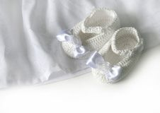 White crochet baby booties. Crochet baby booties with bow and flower Royalty Free Stock Photo