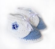White crochet baby booties. Crochet baby boy booties - sneakers with blue star Stock Photo