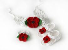 White crochet baby booties and headband with poppy. White crochet baby booties and headband with red flower - poppy Stock Photography