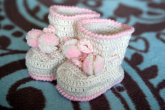 White crocheted booties with pink trim and pom-poms Stock Photo