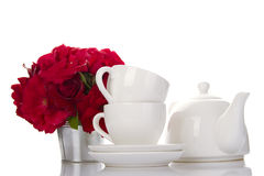 White crockery for tea and a bouquet of roses Stock Photos