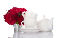 White crockery for tea and a bouquet of roses Royalty Free Stock Image