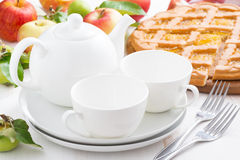 White crockery for the tea party and apple pie on table Stock Photography