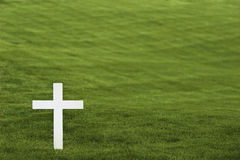 White cross. On a completely uniform green grass background Royalty Free Stock Image