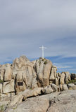 White Cross in Desert Landscape. White Cross on Rocks Honoring the Dead in Wilderness Landscape stock photo
