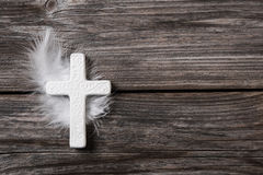 White cross with feather on an old rustic background. Royalty Free Stock Photos
