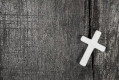White cross on a grey wooden background. Stock Image