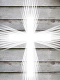 White cross with light rays and old wooden grey background christian symbol of resurrection. White cross with light rays and old wooden board grey background royalty free stock image