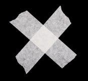 White cross made of adhesive masking tape. Isolated on black Stock Photo