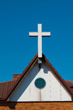 White cross sits proud on church roof. White latin cross representing christian faith stands proud against deep blue summer sky royalty free stock image