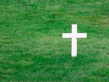 White cross tombstone surrounded by green stock images