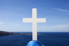 White cross. A cross on top of a church at Santorini, against the Aegean blue Stock Image