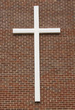White crucifix on brick wall. Close up of white crucifix attached to brick wall building royalty free stock image