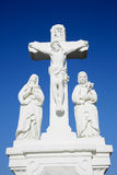 White crucifix sculpture and blue sky background Stock Image