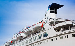 White cruise liner. With portholes mooring in the sea port. Luxury cruise ship at blue sky background. Ocean liner with perspective view Stock Image