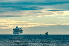 Cruise liner at summer. White cruise liner moving to the sea at cloudy day Stock Photo