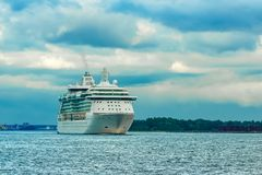 Cruise liner at summer. White cruise liner moving to the sea at cloudy day Stock Photos