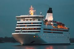 White cruise liner. White passenger ship sailing in evening in still water Royalty Free Stock Image