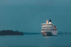 White cruise liner. White passenger ship sailing in evening in still water Stock Images