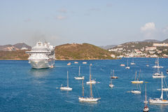 White Cruise Ship in Bay with Many Sailboats Stock Image